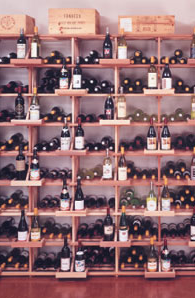 a wine shelf with bottles in both upright and side-lying positions.